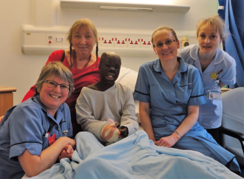 Perlucia with Bronwen Jones, her foster mother for seven continuous years and wonderful nurses at Queen Victoria Hospital, in East Grinstead, West Sussex, UK after complex hand and nose procedures in 2019 by surgeons Asit Khandwala, Baljit Dheansa, Ed Pickles and colleagues
